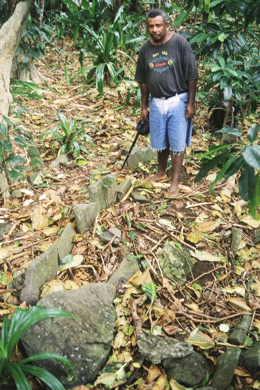 Wolman montre les traces de Dagmel, un hameau abandonné dans la forêt – et notamment une ancienne plateforme de pierres réservée aux dignitaires, mentionnée dans l'un des récits volow. (île Motalava, Vanuatu, juillet 2003). Photo A. François